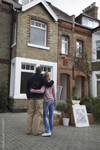 Couple looking at house with possessions outside