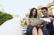 Young couple sitting on stairs reading map, portrait