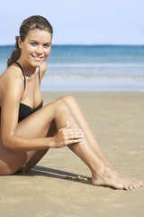 Young woman in swimsuit applying sunscreen on beach