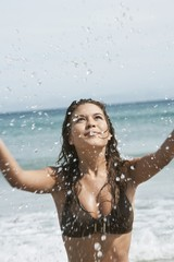 Young Woman Splashing in Surf at Beach
