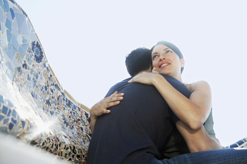 Young couple hugging on stone bench, portrait, low angle view
