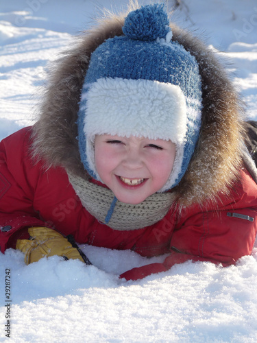 The boy lay on the snow in the bright winter clothes