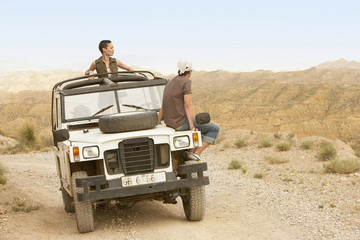 Couple sitting on stationary four wheel drive vehicle in desert