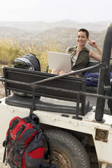 Woman using laptop sitting in back of four wheel drive car, in desert, portrait
