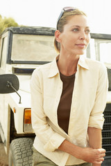 Woman standing in front of four wheel drive car, outdoors