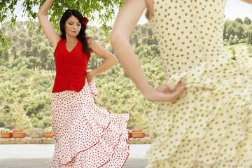 Two women flamenco dancing outdoors.