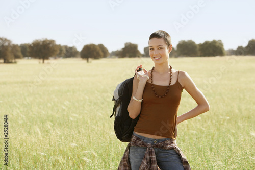 Female hiker holding backpack, standing in field, portrait