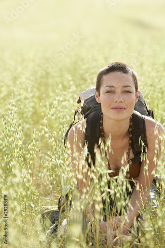 Female hiker squatting in long grass, portrait