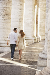 Couple walking between pillars, Rome, Italy, back view