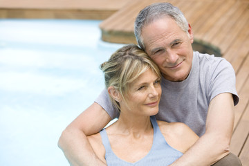 Middle-aged couple sitting embracing by swimming pool, portrait