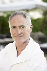 Middle-aged man in bathrobe outdoors
