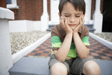 Sad little boy sitting on front steps of house, close up
