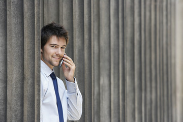 Businessman between pillars outside building talking on phone, portrait