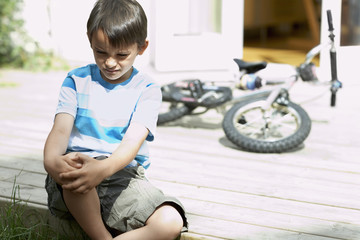 Sad little boy sitting on porch of house