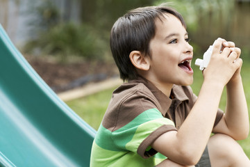 Little boy on slippery slide in park using inhaler
