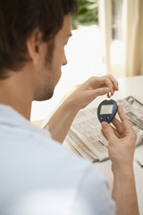 Man Using Blood Sugar Meter in living room