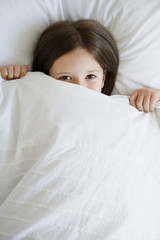 Little girl in bed pulling covers over face, portrait, high angle view