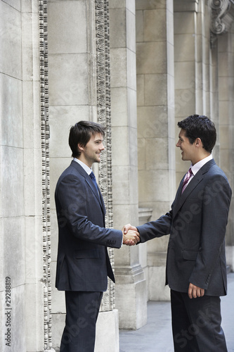 Two businessmen shaking hands outside building