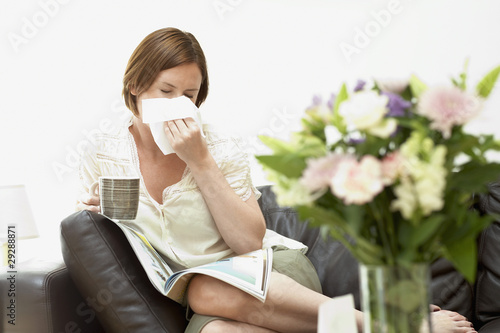 Woman sitting on sofa blowing nose