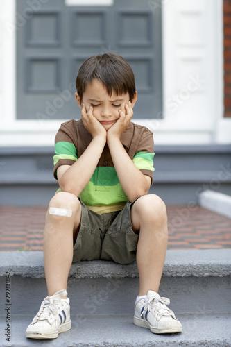 Sad little boy sitting on front steps of house