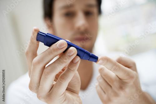 Man using lancelet on finger in bathroom, close up