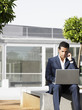 Businessman sitting alone in plaza using laptop and cell phone
