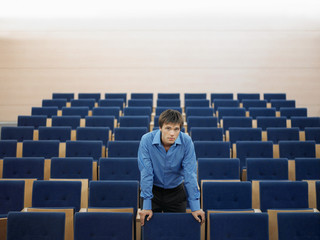 Businessman standing alone leaning on chair in Auditorium, portrait