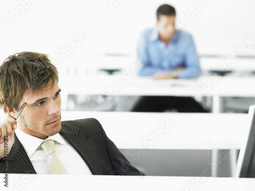 Businessman at desk contemplating in front of computer
