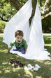 Young boy in back yard crawling out of tent made of bed sheet, portrait