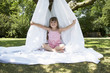 Young girl in backyard sitting in tent made of bed sheet