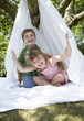 Young boy and girl in backyard sitting in tent made of bed sheet