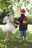 Girl and boy standing in park dressed up as fairy and fireman