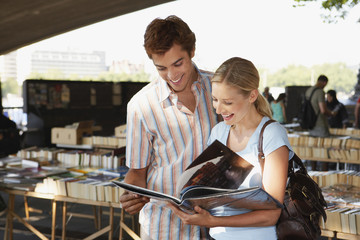 Young couple looking at book in inner-city book market