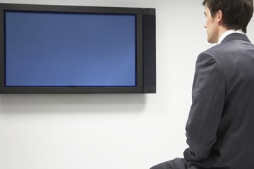 Businessman Looking at Flat Panel Television