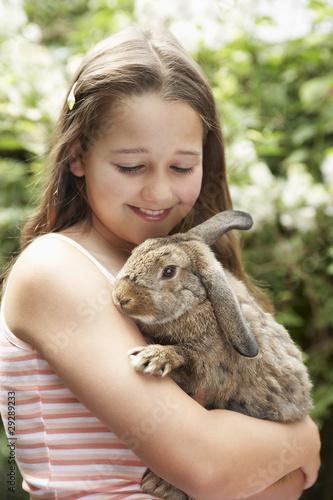 Girl in backyard holding bunny rabbit