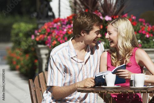Young couple sitting at outdoor cafe laughing and holding guidebook