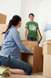 Woman unpacking box, man looking