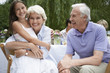 Grandparents with granddaughter 10-12 sitting at table in garden
