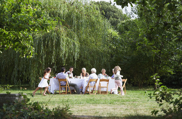 Family eating at table in garden