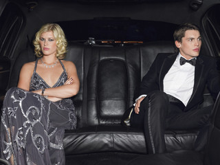 Couple in evening wear in back of car