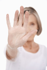 Senior woman holding up palm of hand, studio shot