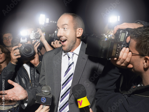 Man surrounded by paparazzi
