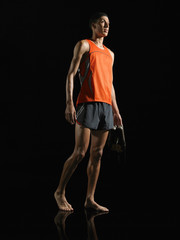Athlete standing, holding shoes, low angle view