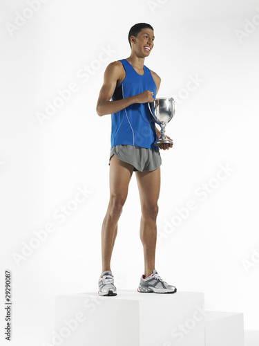 Athlete standing, holding trophy