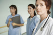 Serious Physician with Nurses in hospital corridor, focus on physician, portrait