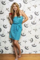 Woman standing by floral print wall Drinking Martini, portrait
