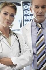 Doctors standing by brain scan images, portrait