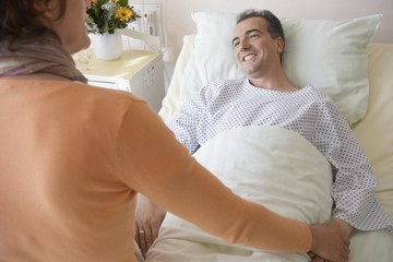 Visitor Comforting Patient in Hospital
