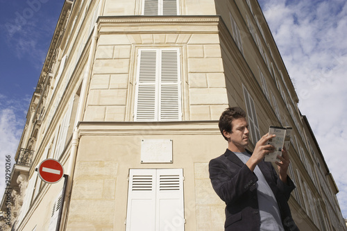 Paris, France, Man studying guide book in front of apartment block