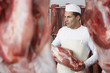 Butcher holding slab of meat, Working in Meat Locker